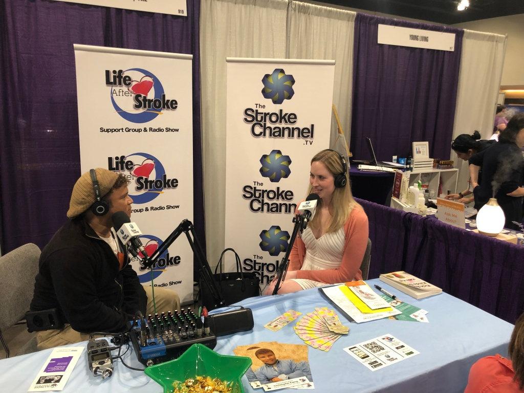 [Image description (alt text in image): a photo of Christopher Ewing and Ashley Jacobson sitting at a booth with radio microphones and banners for The Stroke Channel and Life After Stroke show behind them.]